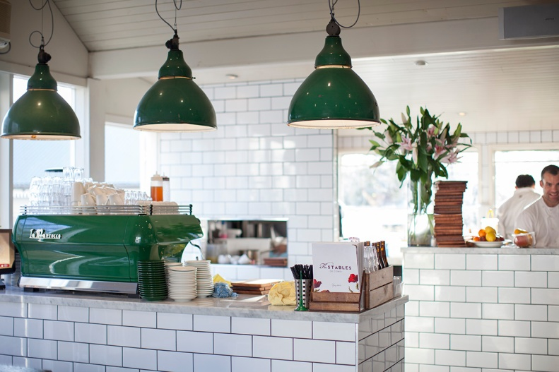 green pendant lamps, glossy white tiles & a shiny coffee machine