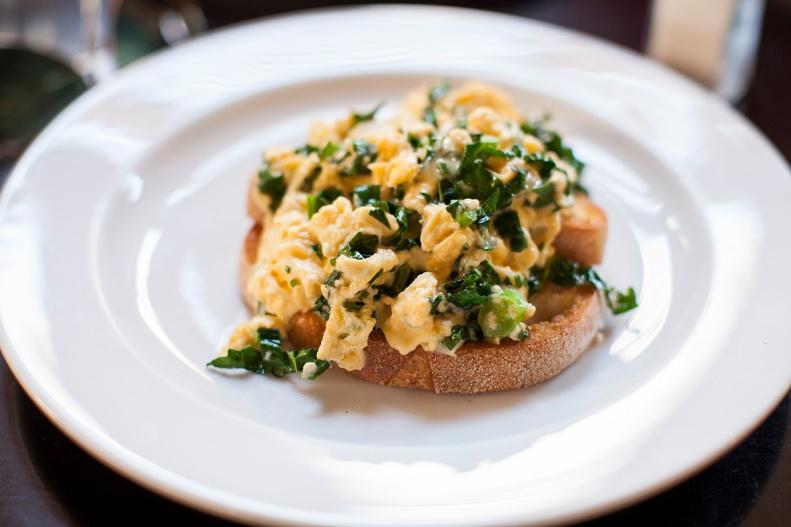 scrambled eggs w/ parmesan, baby cavolo nero & soft herbs