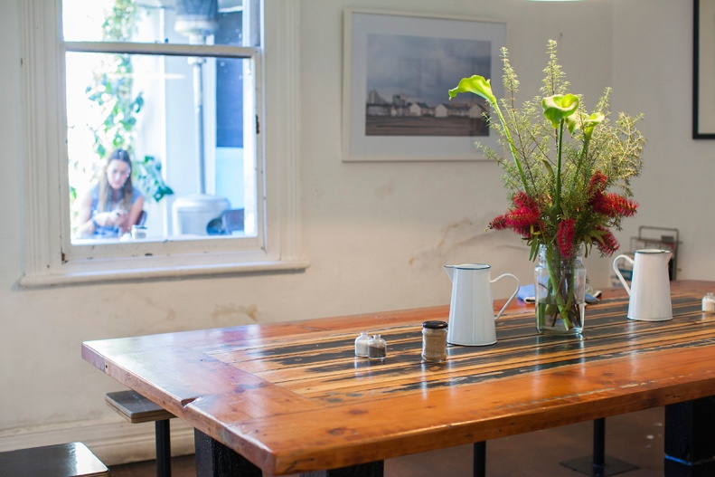 enjoy the communal wooden table in a cosy corner of the cafe